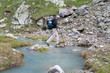 Hikier with backpack is walking in Caucasus mountains in Bezengi