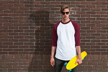 Urban fashion skateboarder with sunglasses posing in front of br