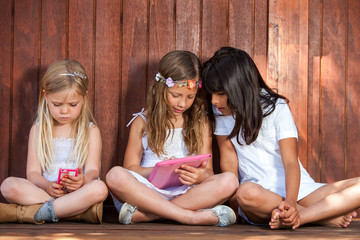 Three girls playing with tablet and smart phone.