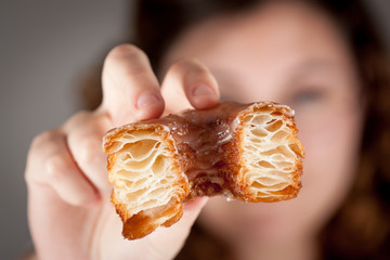 Croissant and doughnut mixture being held by a girl