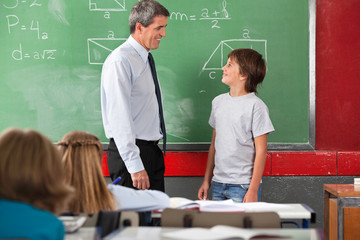 Teacher And Schoolboy Looking At Each Other In Classroom