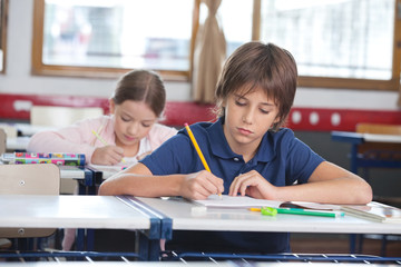Little Boy Writing Notes With Classmate In Background