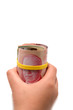 Hand holding a roll of 50 dollars Canadian with yellow plastic b