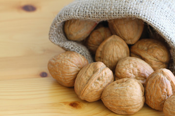 Whole walnuts in jute bag on wooden surface, close up