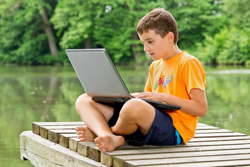Jugendlicher sitzt mit Notebook auf dem Schoß am  Teich