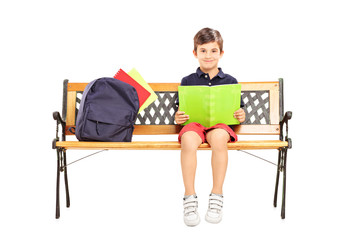 Schoolboy sitting on a wooden bench and reading a book