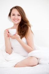 woman sitting on bed with cup