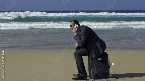 Businessman sitting on suitcase on the beach and hearing great n