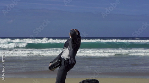 Businessman, suitcase on the beach and talk by cellphone, slow m