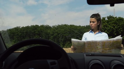 Female car driver lost in the countryside, reading map