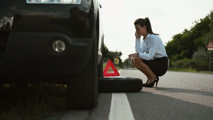 Young woman with flat car tyre calling tow truck by phone