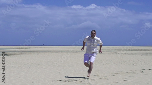 Young man in white clothes jumping on the beach, slow motion sho