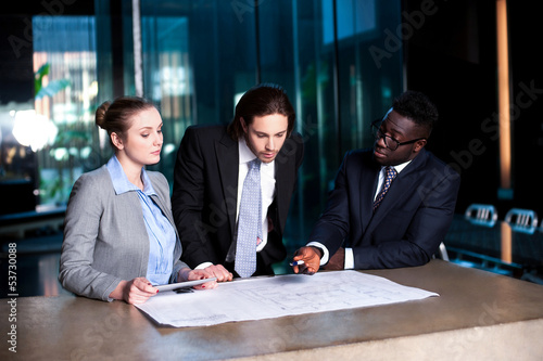 Business team of three reviewing project plan
