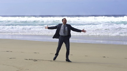 Happy businessman dancing on the beach, slow motion shot at 240f