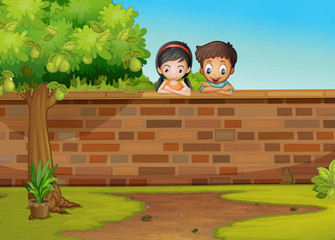 A girl and a boy leaning over the concrete fence