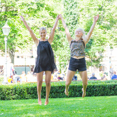 Two Blonde Girls Jumping at Park