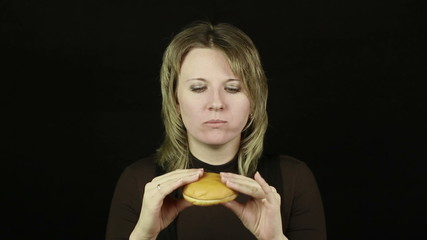 Woman eating hamburger on a black background