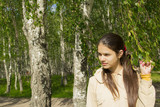 A girl walks in the birch forest.