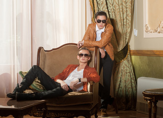 Indoors portrait of two young men in sunglasses