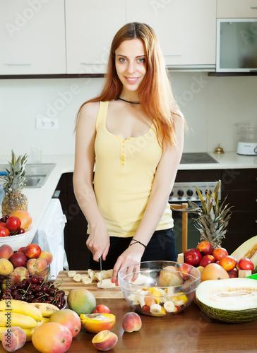 woman cutting banana for fruit salad
