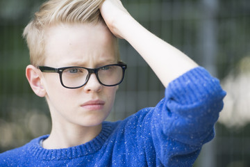 Portrait confident blond teenager with glasses