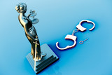 Themis statue and handcuffs over white background