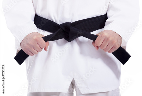 Martial arts man tying his black belt, isolated on white