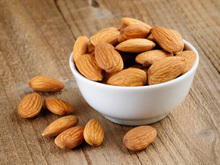 Almonds in bowl on wooden table