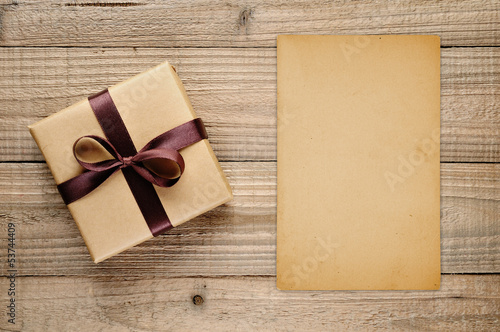Vintage gift box and blank card on wooden background