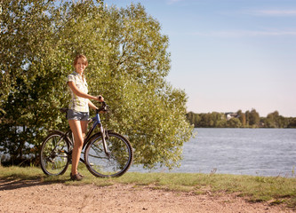 Woman with a Bike on Beautiful Nature Background