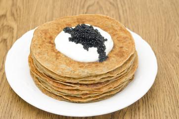 potato pancakes with sour cream and caviar, selective focus
