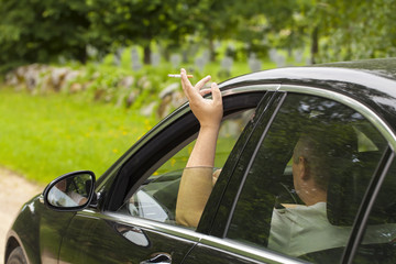 Driver  with a cigarette in hands sitting in car
