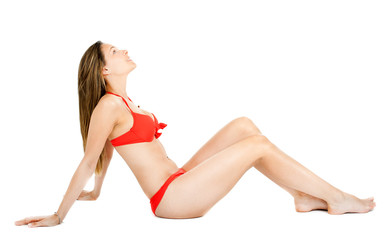 Woman in bikini sitting on the floor isolated on white