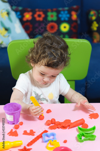 Little baby girl child playing plasticine on the table