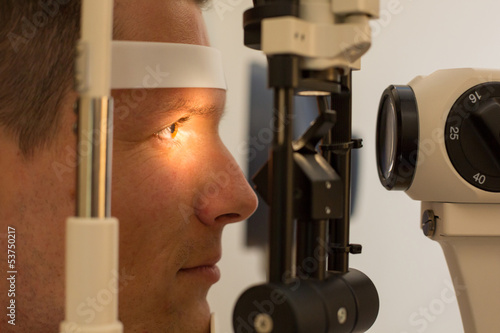 Patient at slit lamp of optician or optometrist - 53750217