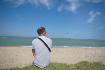 man on the beach watching at kite surfers