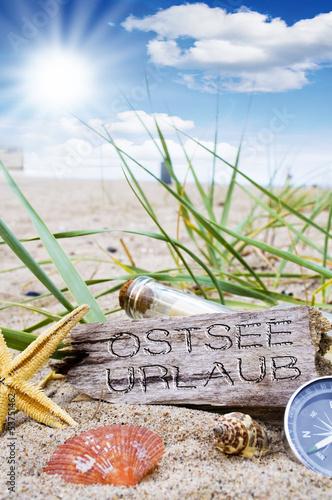 Treibholz mit Strandgut und Flaschenpost und Kompass