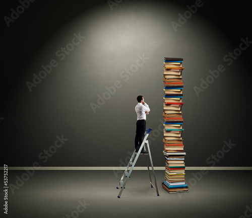 businessman looking at pile of books