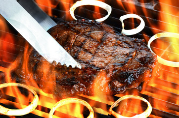 Steak on flaming grill with onions