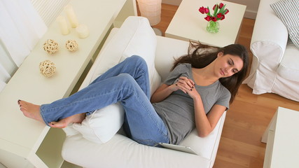 Happy woman talking and smiling while lying on couch