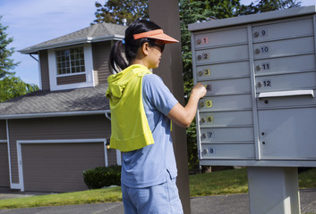 Mature woman checking her mail in front of her house