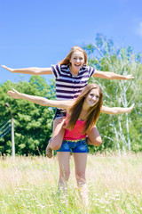 Two teenage girl friends having fun outdoors