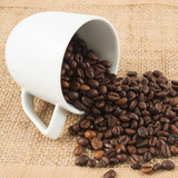 Fototapety Cup full of coffee beans over hessian cloth
