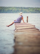 Pregnant woman sitting on the dock