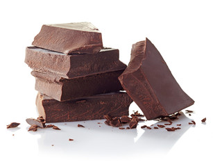 Heap of broken chocolate pieces on white background