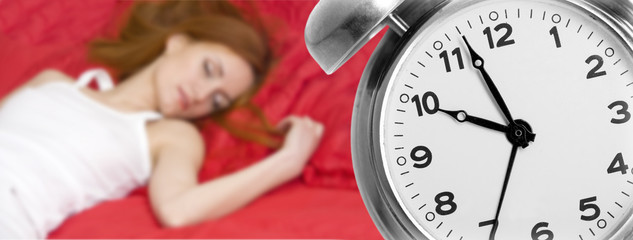Alarm clock and sleeping young woman