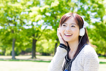 young asian woman listening music in the park