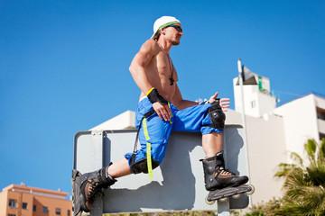 junger sportlicher mann mit inline skates im sommer