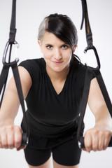 Sportlerin trainiert mit Schlingen