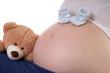 schwangere Frau mit kleinen Babyschuhen und Teddy